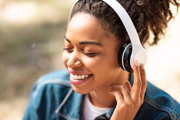 Black Lady In Headphones Listening Music With Eyes Closed Outside - Stock Photo - Images