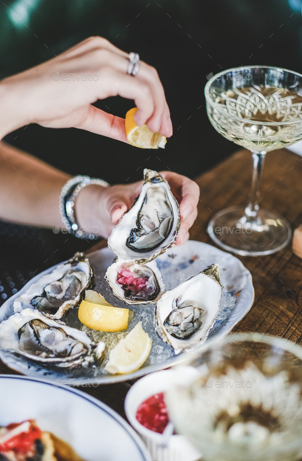 Woman squeezing lemon juice to oysters in plate with ice - Stock Photo - Images