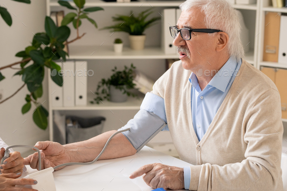 Aged man asking for medical advice during procedure of measuring blood pressure - Stock Photo - Images