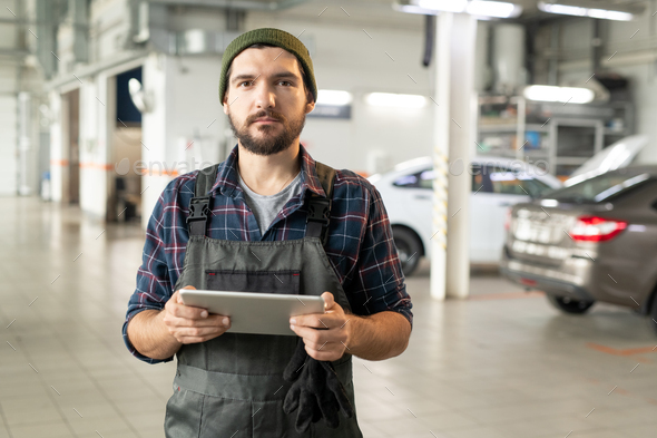 Young bearded worker of contemporary car service using tablet in workshop - Stock Photo - Images