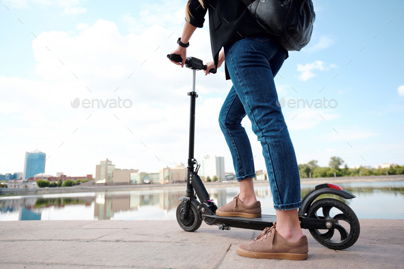 Contemporary young female on electric scooter standing in front of riverside - Stock Photo - Images