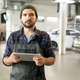 Young bearded worker of contemporary car service using tablet in workshop - PhotoDune Item for Sale