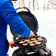 Man grilling steaks on a portable BBQ, Snowy winter barbecue - PhotoDune Item for Sale