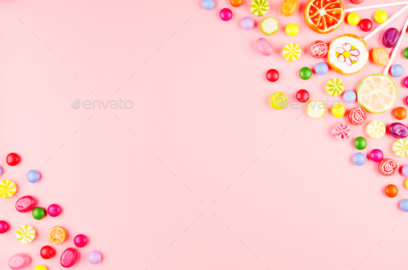 Flat lay view at sweet background of different type color and taste candies on pink. Space for text - Stock Photo - Images