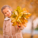 Portrait of adorable little girl outdoors at beautiful warm day with yellow leaf in fall - PhotoDune Item for Sale