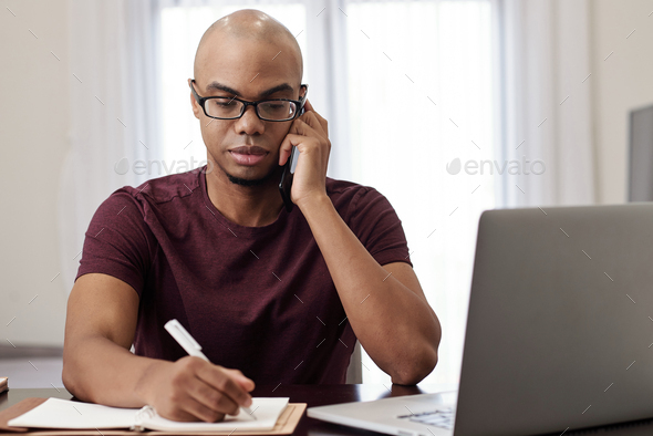 Businessman writing in planner - Stock Photo - Images