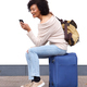 smiling travel woman sitting on suitcase with cellphone by white wall - PhotoDune Item for Sale