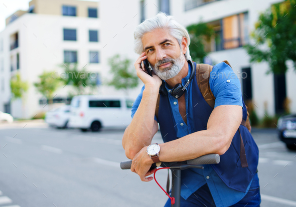 Mature man commuter with electric scooter outdoors in city, using smartphone - Stock Photo - Images
