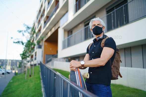 Mature man commuter with face mask and skateboard outdoors in city, coronavirus concept - Stock Photo - Images