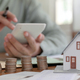 Close-up shot of Houses models and coins with people using a calculator to calculate home expenses. - PhotoDune Item for Sale