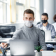 Attractive worker at workplace takes pencil in his hands behind laptop. Guy in protective mask sits - PhotoDune Item for Sale