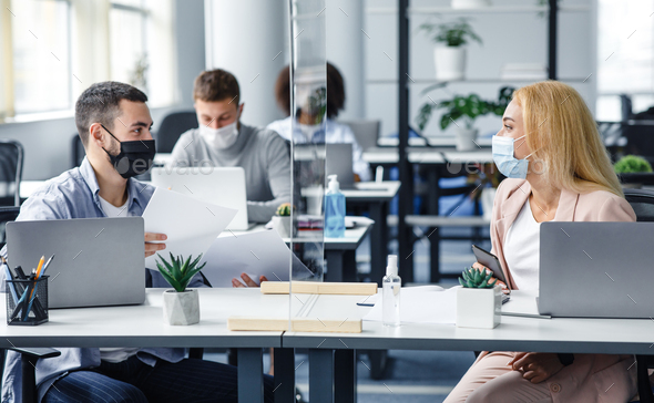 New normal and communicate with protection. Millennial man and woman in protective masks work with documents in protective glass in office interior during coronavirus quarantine, free space
