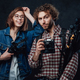The team of two young photographers holds a digital camera and lighting equipment in studio - PhotoDune Item for Sale