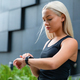 Woman checking her fitness smart watch device - PhotoDune Item for Sale