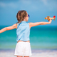 Happy little girl with toy airplane in hands on white sandy beach - PhotoDune Item for Sale