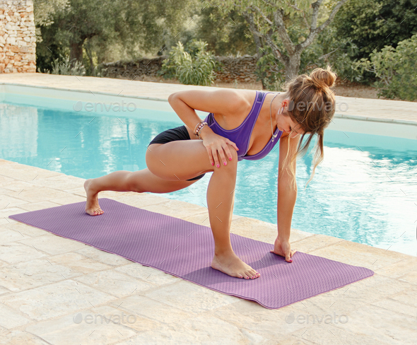 Young woman practicing Lizard Yoga pose near a pool - Stock Photo - Images