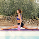 Young woman practicing Front Splits pose near a pool - PhotoDune Item for Sale