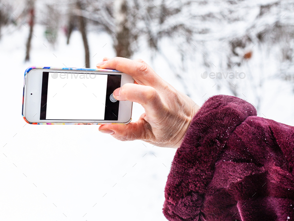 female hand takes picture by smartphone in winter - Stock Photo - Images