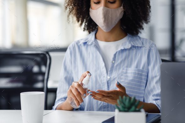 African american woman in protective mask using antiseptic to disinfect hands at workplace in - Stock Photo - Images