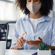 African american woman in protective mask using antiseptic to disinfect hands at workplace in - PhotoDune Item for Sale