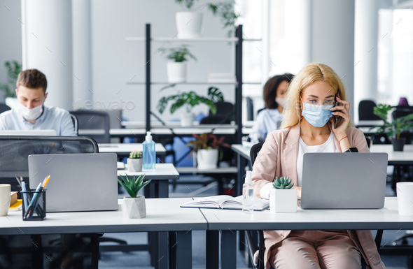 Working with client by phone remotely during COVID-19 outbreak. Millennial woman in protective mask - Stock Photo - Images