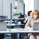 Working with client by phone remotely during COVID-19 outbreak. Millennial woman in protective mask - PhotoDune Item for Sale