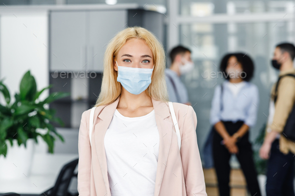 Modern manager returns to work after quarantine. Focus on attractive blonde woman in protective mask - Stock Photo - Images