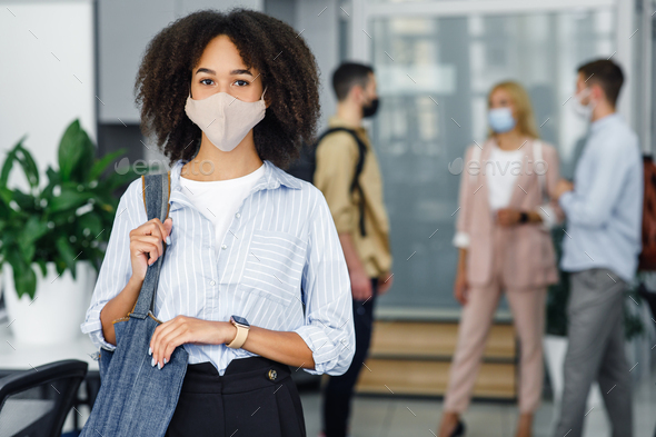 Social distancing and office work with colleagues. Attractive young african american woman with bag - Stock Photo - Images