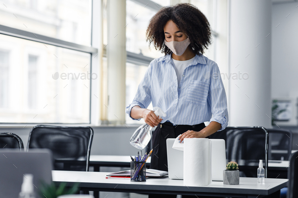 Disinfection from coronavirus in coworking place. African american young woman in protective mask - Stock Photo - Images