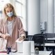 Hygiene in workplace in coworking office. Blonde business woman in suit and protective mask cleans - PhotoDune Item for Sale
