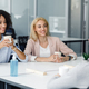 Smiling european and african american businesswomen with cups communicating with guy through glass - PhotoDune Item for Sale