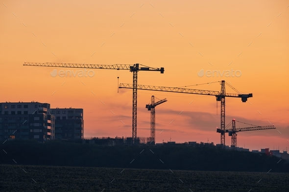 Building activity on contruction site at sunrise - Stock Photo - Images