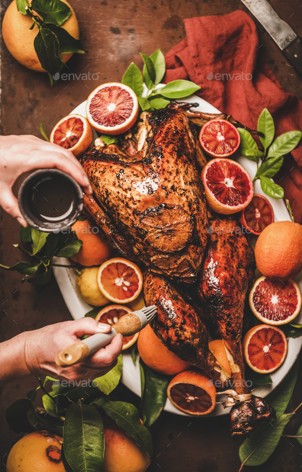 Womans hand putting oil on whole roasted turkey for holiday - Stock Photo - Images