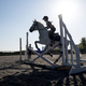 Silhouette of female rider jumping hurdle in a paddock on a grey horse - PhotoDune Item for Sale