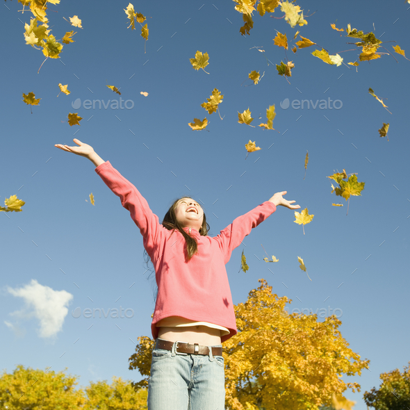 A girl throwing dried fallen autumn leaves high into the air. - Stock Photo - Images