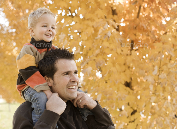 An adult parent and child, father and son under a canopy of orange autumn leaves.