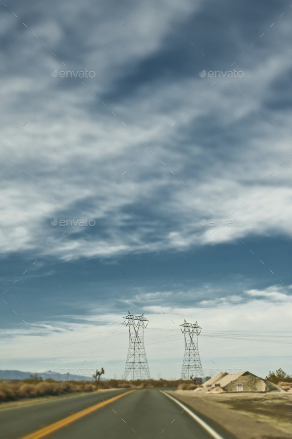 An open road, two lane blacktop, road trip, electricity pylons and wires