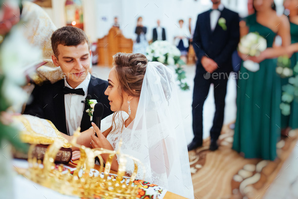 Groom putting a ring on bride's finger during wedding - Stock Photo - Images