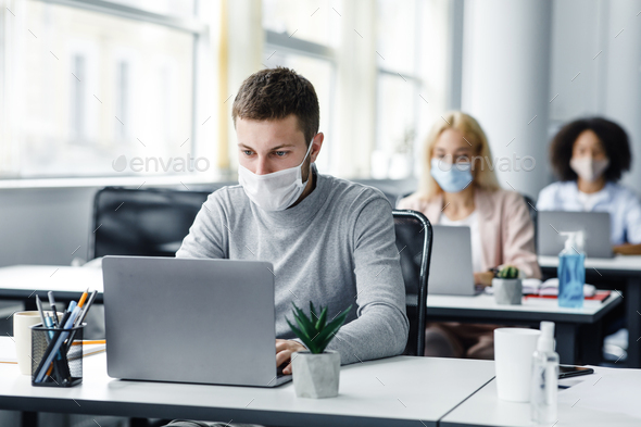 Coworking office and safe work during coronavirus epidemic. Young man with face mask back at work in office after lockdown and looks at laptop, like multiracial colleagues, free space