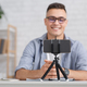 Modern hobby and remote work online. Focus on smartphone on tripod and smiling guy with glasses - PhotoDune Item for Sale