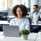 Employee works in coworking office during coronavirus. Smiling african american millennial woman - PhotoDune Item for Sale