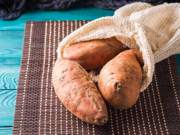 Sweet potato in a reusable cotton mesh bag - Stock Photo - Images