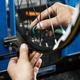 Bicycle repair in workshop, man tightens spokes - PhotoDune Item for Sale
