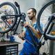 Bicycle repair in workshop, man checks mechanisms - PhotoDune Item for Sale