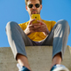 Young man using his smartphone sitting on a ledge outside - PhotoDune Item for Sale