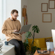Young bearded freelancer using laptop while networking on windowsill - PhotoDune Item for Sale