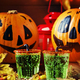Halloween composition with festive green drink and smiling drinking pumpkins - PhotoDune Item for Sale