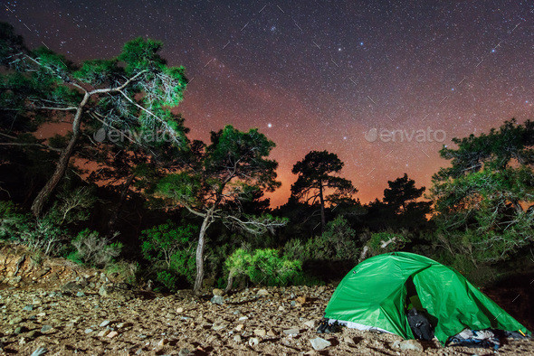 Camping under the stars. Green solo tent under dark night sky full of stars and constellations