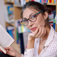 Beautiful woman wearing glasses reading a book in the book shop. - PhotoDune Item for Sale