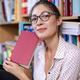 Beautiful woman with glasses and book in a book shop - PhotoDune Item for Sale